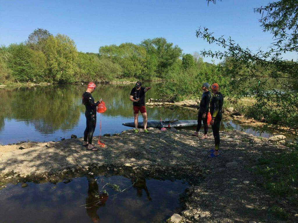 Drei Personen im Neoprenanzug bereiten sich auf ein Freiwasser-Schwimmtraining vor